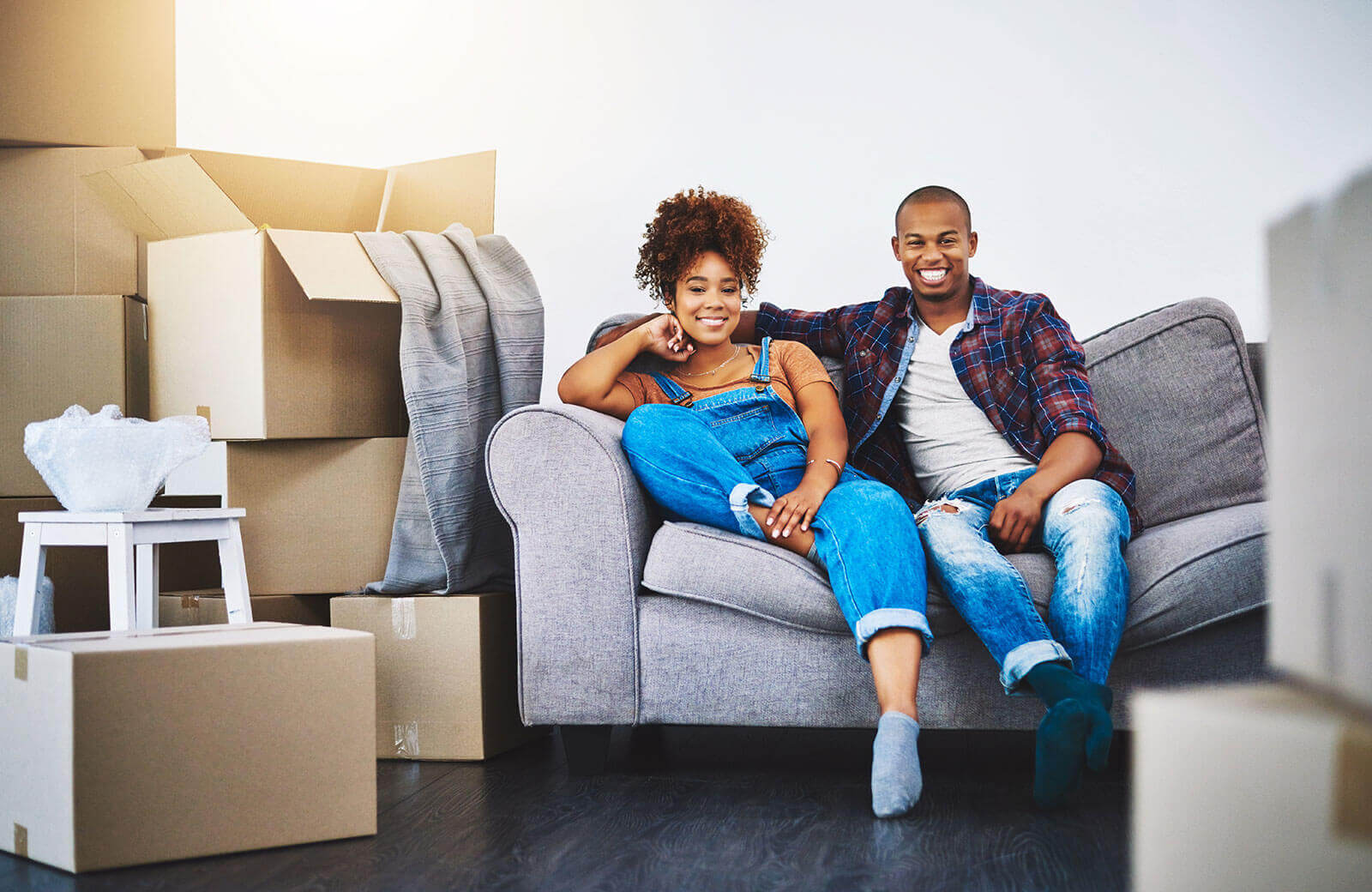 Couple sitting on a couch near their packaged furniture